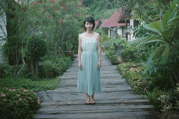 Woman wearing long dress standing on boardwalk