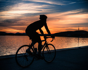 Australia, Canberra, Russell, Silhouette of cyclist at sunset near Lake Burley Griffin