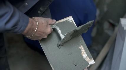 Man applying glue to ceramic tile