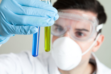 Scientist looking at liquid in test tubes