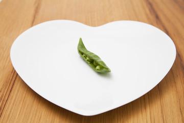 Pea pod on heart-shaped plate