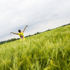 Rear view of woman in field with outstretched arms