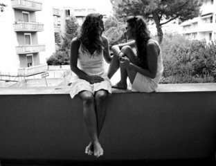 Young female twins talking outdoors