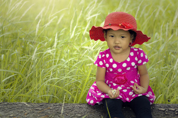 Portrait of girl in dress and hat sitting in grassy field