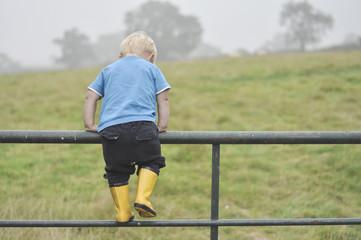 Boy climbing metal fence