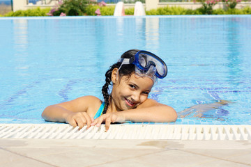 Smiling cute little girl (6-7) having fun in swimming pool