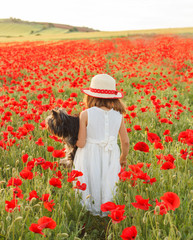 Girl (4-5) with dog in field of poppies
