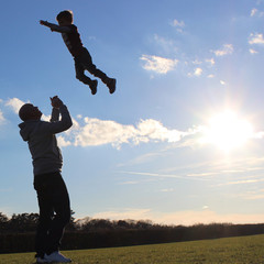 Father throwing son (2-3) into air