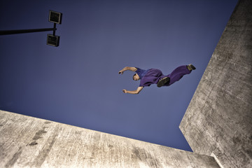 USA, Colorado, Man making parkour jump across concrete structure