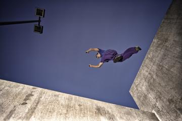 USA, Colorado, Man making parkour jump across concrete structure