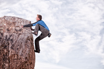 USA, Colorado, man rock climbing on large boulder