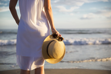 Rear view of woman in white dress standing on beach and holding hat