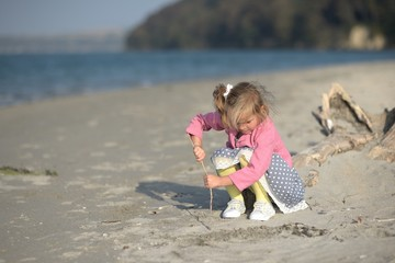 Girl (2-3) with stick on beach