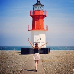 Woman standing in front of lighthouse