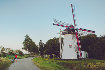 Netherlands, Man standing on road next to old fashioned windmill