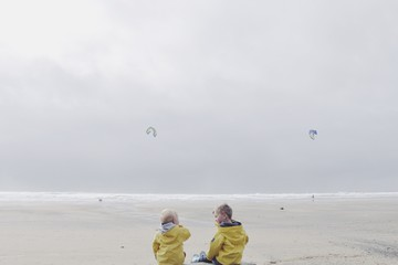Rear view of boys sitting on the beach