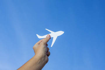 Boy's hand holding paper-made airplane against blue background