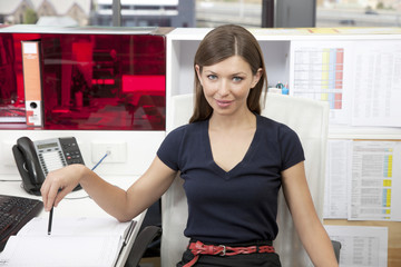 Portrait of young businesswoman at desk in office