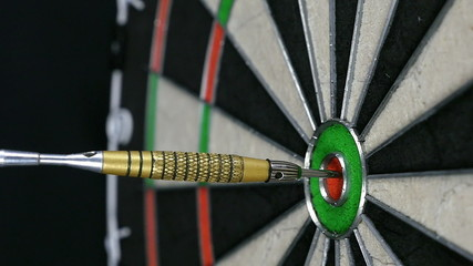 Close up of a single dart hitting the bull's eye on a dart board