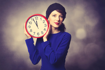women in blue dress with huge clock