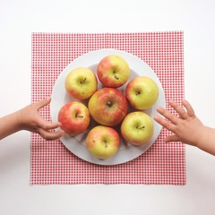Plate of apples with children's hands