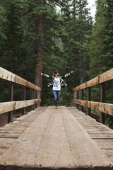 Teenage girl skipping across bridge over river