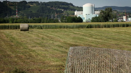Shot of grain field with nuclear power station in the back