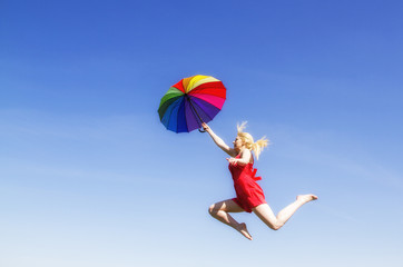 Young woman jumping with colorful umbrella