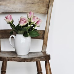 Roses in vase on chair