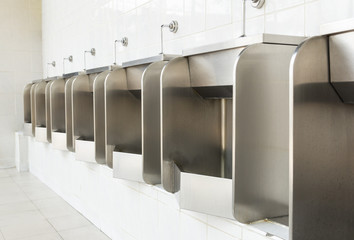 Row of stainless urinals at public restroom
