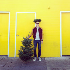 Young man holding small Christmas tree in front of yellow wall