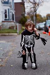 Smiling boy (2-3) in skeleton costume holding chocolate bar