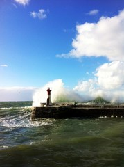 Waves crashing against lighthouse tower