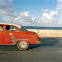 Cuba, Ciudad de La Habana, Havana, Side view of vintage car driving along seaside