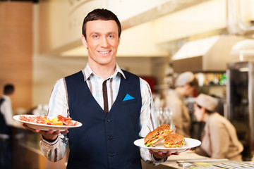 Waiter carrying two plates with sandwich.