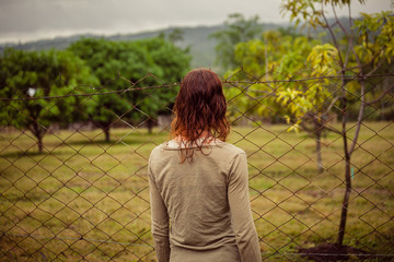 Young woman by fence on farm