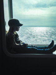 Side view of boy (6-7)  sitting in  window on ferry