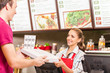 Restaurant worker serving food with smile. - 77440345