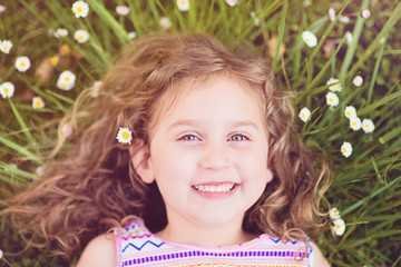 Portrait of smiling girl (4-5) lying in grass