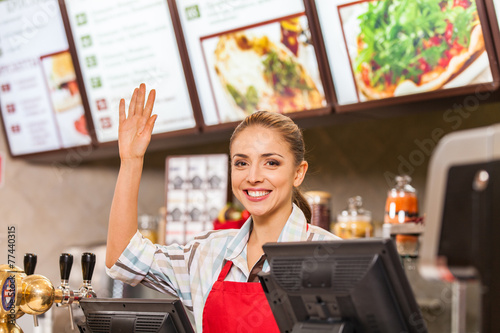 Restaurant worker at cashier smiling at work place. - 77440315
