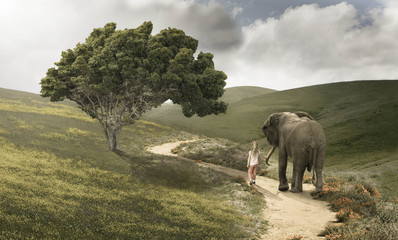 Girl (4-5) and small elephant walking along winding foot trail