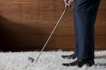 Businessman practicing golf in office