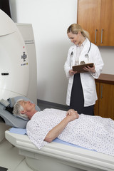 Female doctor with male patient next to MRI Scanner