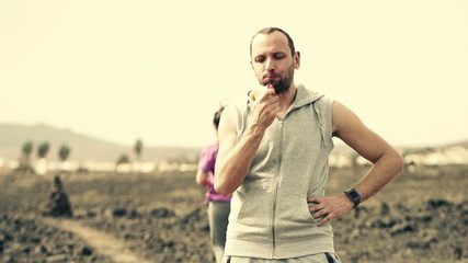 Man eating apple and woman jogging on desert