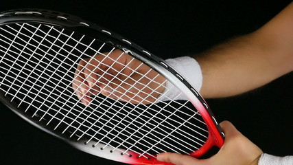 tennis player's hand adjusting the net of his tennis racket