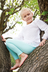 cute girl sitting on a tree in summer