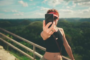 Young woman taking selfie with smart phone on tropical hill