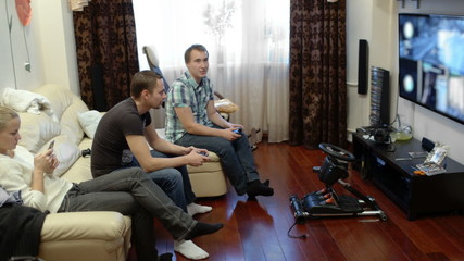 Men playing video game and girl using cell phone