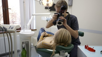 Dentist making shots of womans smile after treatment