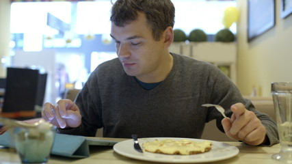 Man using pad and having dinner in cafe